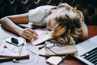 Garota dormindo sob os livros sem motivação para estudar