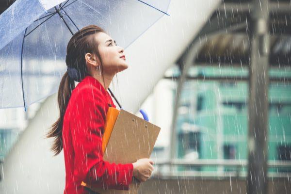 Estudante com livros na mão esperando a chuva passar