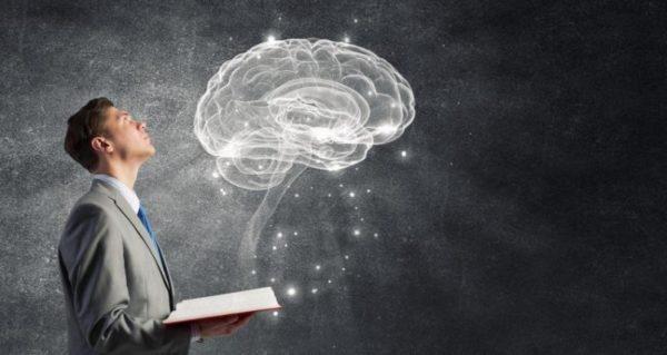 homem com livro da onde se projeta um cerebro