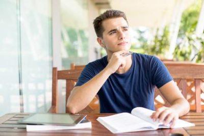 rapaz pensativo estudando sobre uma mesa