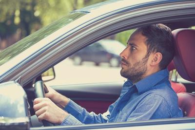 homem dirigindo com aspecto de medo