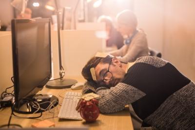 homem deitado sobre a mesa do trabalho descansando