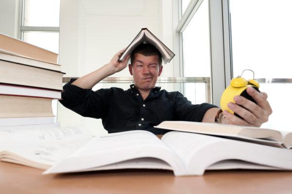 homem olhando para o relogio com livro sob a cabeça