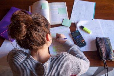 garota organizada com material de estudos na mesa