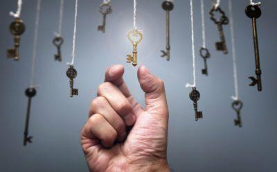 homem alcançando chaves penduradas por cordas