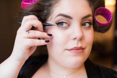 moça gordinha com olhar confiante se maquiando