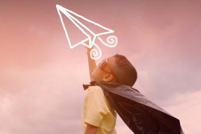 criança vestida de herói lançando avião ao ar