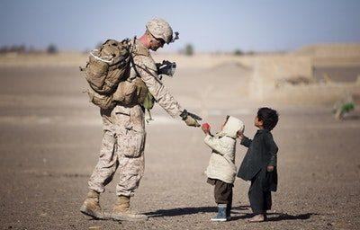 militar servindo comida a crianças necessitadas