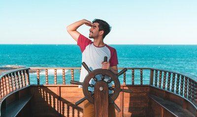 homem navegando barco e sorrindo se divertindo