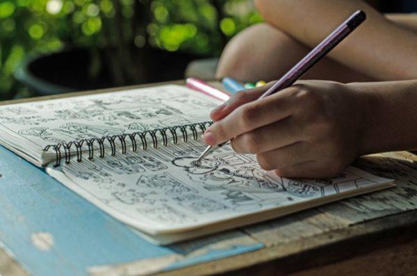 escrevendo em caderno com lápis