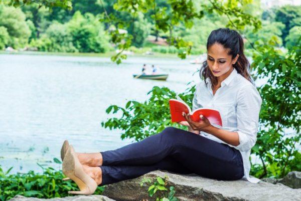mulher lendo livro ao ceu aberto