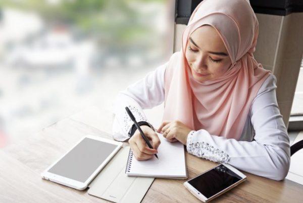 mulher estudando com cadernos e eletrônicos sob a mesa
