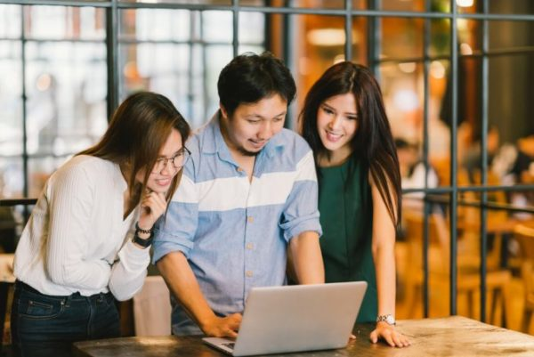 tres estudantes observando computador