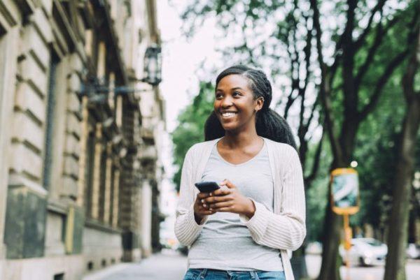 mulher caminhando nas ruas com celular nas mãos
