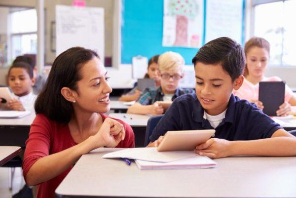 mulher ensinando aluno em sala de aula