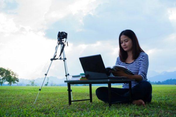 mulher estudando no computador em paisagem sob ceu aberto