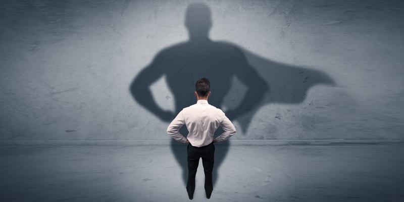 homem diante da sombra de um super-herói
