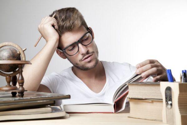 estudante fazendo leitura de um livro sobre a mesa