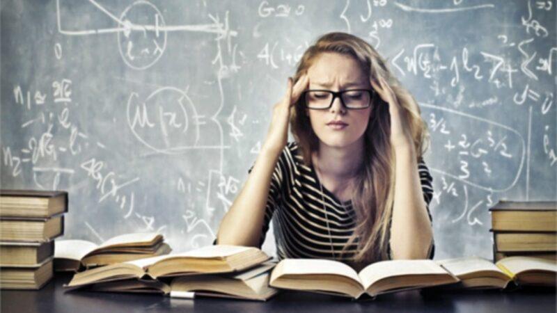estudante forçando a se lembrar diante dos livros