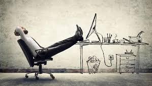 homem com pés esticados sob a mesa ocioso