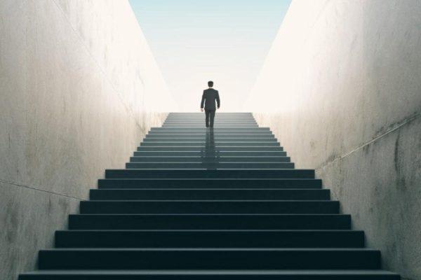 homem executivo subindo escadarias altas