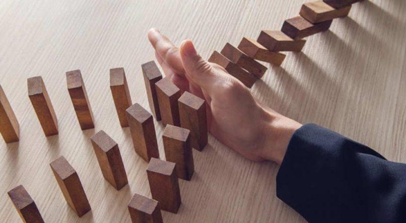 mão reagindo a derrubadas de peças de dominó