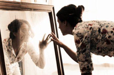 mulher diante do espelho com crise de existencia